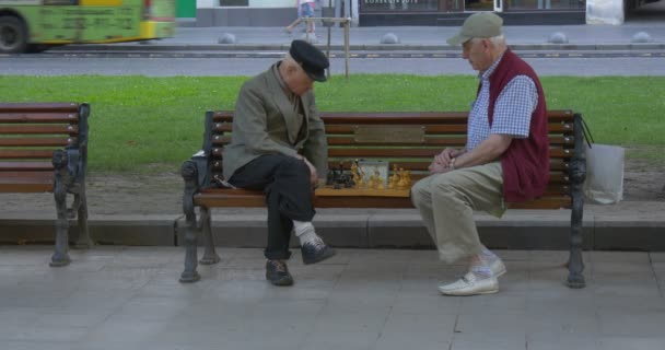 Two Men Are Sitting in Front of Each Other on The Bench, Senior Aged Men in Caps, Playing Chess, Mid Shot