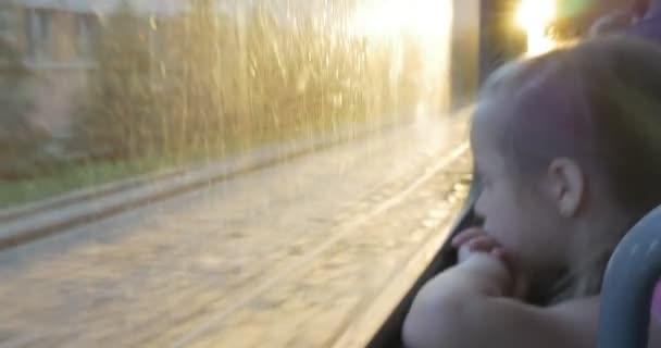 Malá holka blondýnka v růžové košili sedí u okna v autobus, tramvaj, trolejbus, hledám, Lvov Street, budov, tramvaj železniční, stromy