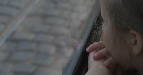 Holčička blondýna v růžové košili je sedící u okna v autobus, tramvaj, hledám, Lvov, holka, železnice za okno, zastavit, pohyb