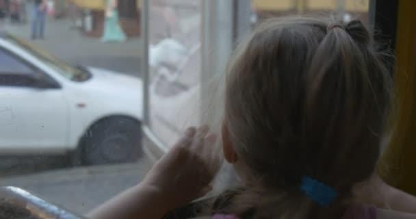 Rózsaszín póló szőke kislány ül az ablak néz az ablakon át Lviv busz, villamos, trolibusz, a lány, mosolygó, beszélő