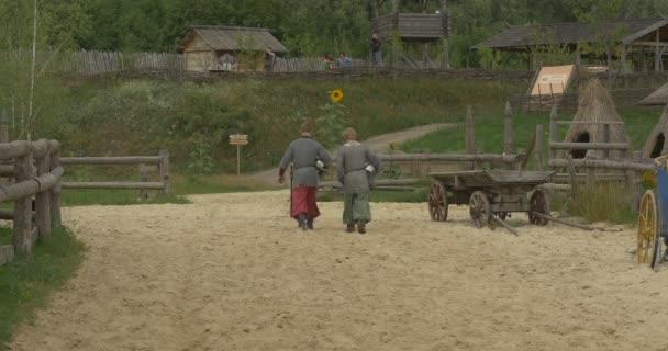 Dva herci, muži ve staré kostýmy jsou odcházet Sandy pole, vozík, slunečnice