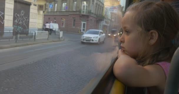 Malá blondýnka sedí v The Window v autobuse, dívali se oknem na Lvov, lidé, osobní, automobily, dívka se naklonil se její hlava