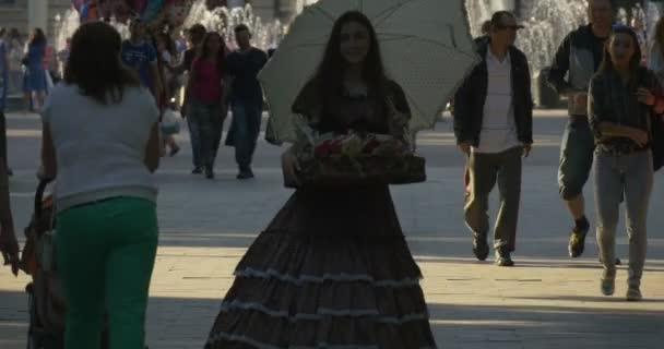 Lidé, páry jsou procházky do uličky, Avenue, Boulevard, Park, fontány na pozadí, dívka v šatech Vintage je prodej cukrovinek, detail
