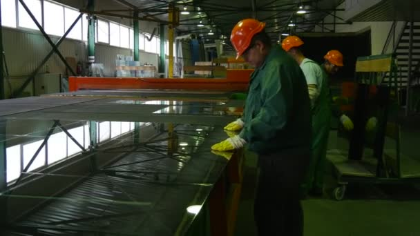 Three Workers are Taking Off the Pieces of Glass After Cutting by Robot, Workers are in Orange Safety Helmets, Production of Glass