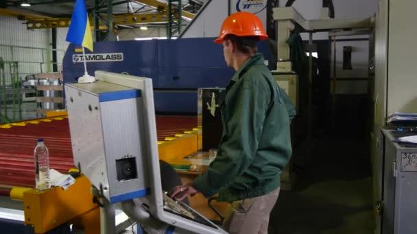 Worker in Orange Helmet, Factory Uniform is Standing at the Machine, Looking at the Machine, Glass Factory Equipment, Ukrainian Flag, Machine Zoom In