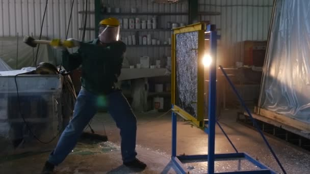 Worker In Uniform And Protective Screen, Yellow Gloves, is Beating the Glass Sheet by Hummer, Testing of Bulletproof Glass, Lamplight