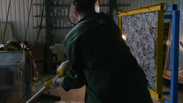 Worker In Uniform And Protective Screen, Yellow Gloves, is Beating the Glass Sheet by Hummer, Lamplight, Testing of Bulletproof Glass