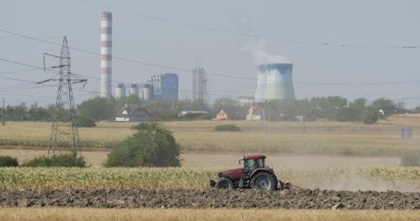 Tractor is Driven by the Fiels Landscape Dry Straw High-Voltage Tower Wires Tubes of the Factory Smoke from Tubes Houses on a Horizon Trees Blue Sky