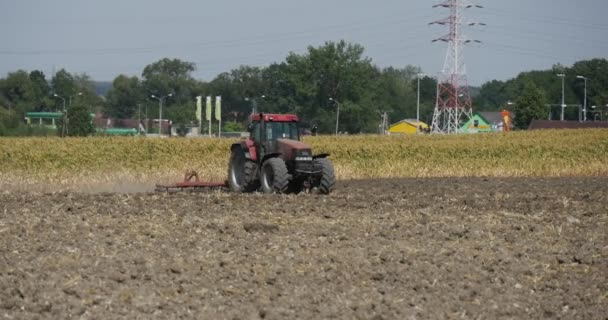 Tractor Distantly Tractor is Plowing The Field Plow Tractor is Approaching Field Road and Street Lamps High-Voltage Tower Tractor Moves to the Right