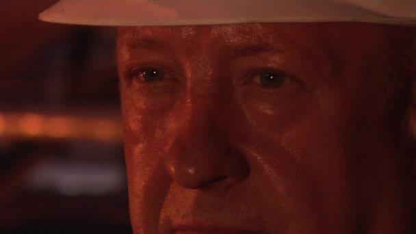 Pracovník tvář Close Up v bílém helmu Factory Logo na helmu muž se zakryl oči s rukou pracovníků muži v ochranných přileb