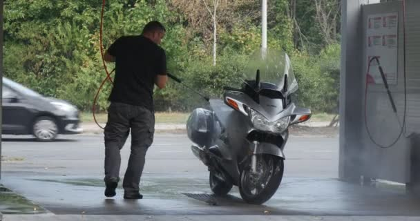 Man Washes His Silver Motorbike At The Carwash Two Bicyclers Pass By Cars Go By Paved Road Behind The Carwash Wet Asphalt Green Trees Summer Day