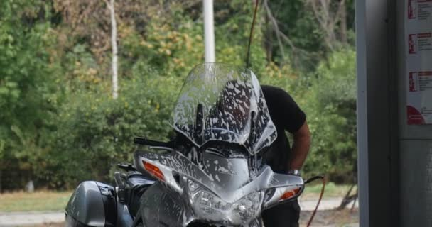 Man With Brush Carefully Washes His Silver Motorbike At The Carwash The Windshield In The Suds Car Passes By Summer Day Outdoor