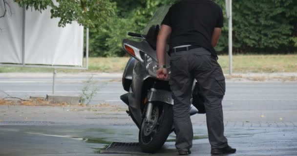 Man Stands Near His Silver Motorbike Washes Front Wheel Of His Bike Than Put Cleanser Back To His Trunk On The Background Cars Go By Paved Road