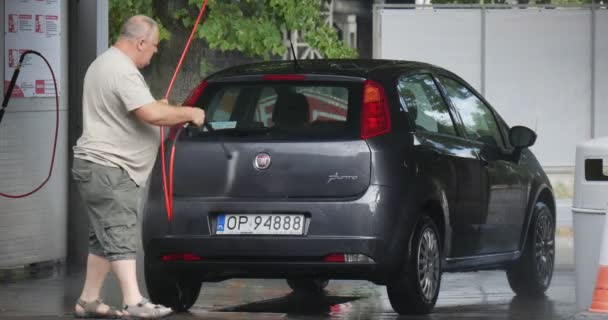 Man At The CarWash Washes His Car Compact Hatchback Grey Fiat Punto On The Background Cars Go By Paved Auto Road outdoor