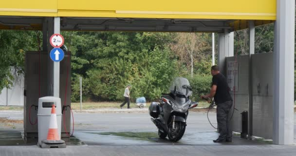 Man With Brush Washes His Silver Motorcycle At The Carwash Behind The Carwash Cars Go By Paved Road And Man Go With Cart Summer Day Outdoor