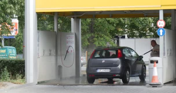 Man On A CarWash Washes His Car Compact Hatchback Grey Fiat Punto On The Background Cars Go By Paved Auto Road Outdoor