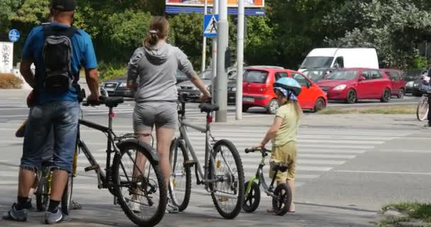 Man Woman And Two Kids With Bicycles Wait Near The Crosswalk Cars Go By Paved Auto Road In Opole Poland Sunny Summer Day