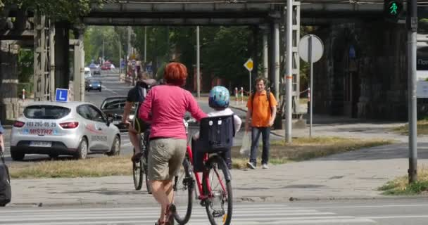 Men Ride On The Bicycles Woman With A Kid On The Baby Seat On The Bicycle Man With A Bag Walks At The Crosswalk Many Different Cars Go By Paved Road In Opole Poland