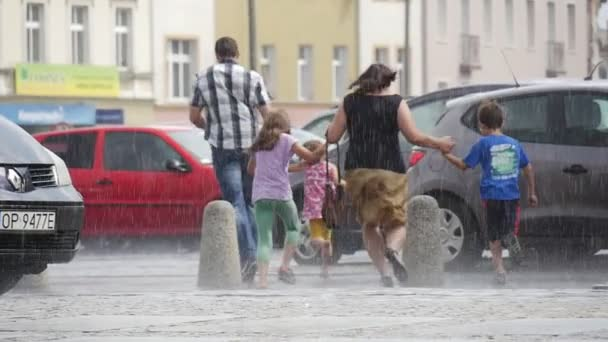 Man And Woman With Three KIds Run In The RAin Without Umbrellas Wet Road Buildings Cars Downpour Summer DAy In Opole Poland Back View Slow Motion