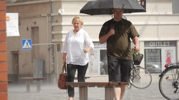 Elderly Woman And Man With Umbrella Walk in The Rain Building Parked Bicycles Benches Traffic Signs Slow Motion Close View
