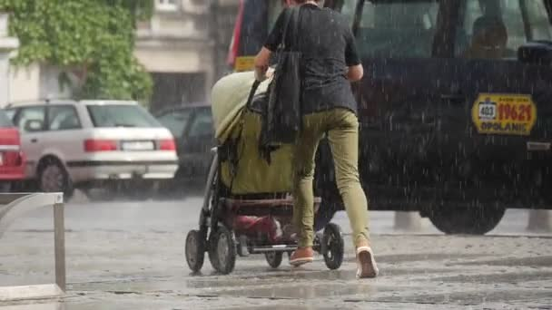 Young Woman With Baby Pram Runs In The Rain Without Umbrella Near Stand Parked Bicycles And Cars Downpour In Opole Poland Close View Slow Motion