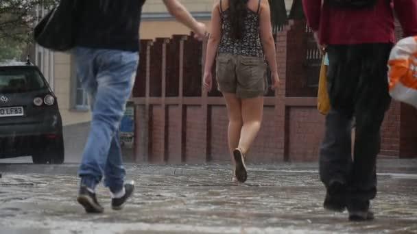 Tři ženy a muže chodit na vlhký chodník v dešti napravo od těch cihel plot deštivé letní den v Opole Polsko zpomalené zblízka