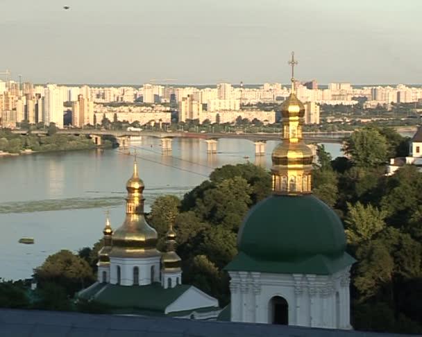 Kyjev panoráma Kyjevskopečerská lávra zelené báně zlaté báně Zoom v Dněpru most přes řeku zelené stromy, modré jasno