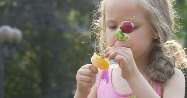 A Little Girl is Eating Pieces of Various Fruits on the stick within her fingers