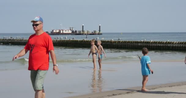 Kids Play In The Water Man And Woman Walk On The Sea Shore Group Of Elderly People Walk On The Sand Barge Works At The Sea Creation Of Dam Groynes Summer Day