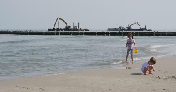 Dvě děti hrají na pobřeží čluny s bagrem na moři Aggradation půdy vznik Dam průplavní stavebních prací na moři Leba Polsko