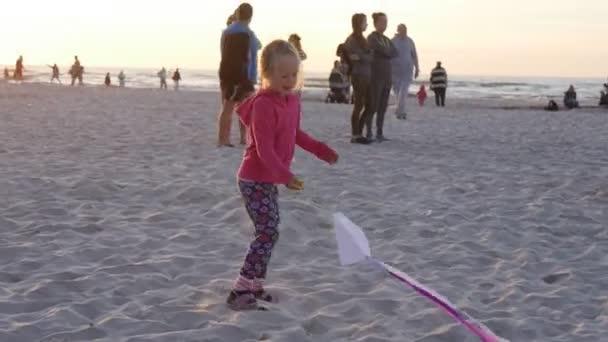 Mosche di ragazza la ragazza piccola Kite sta ondeggiando persone famiglie siluette sono a piedi alla spiaggia bambini giocano Polonia Leba Festival internazionale degli aquiloni