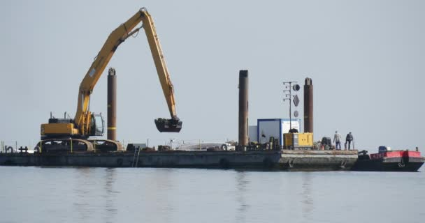 Working Excavator On The Board Of The Barge Another Cargo Barge Stands Near People Walk On The Board Of The Barge Construction Works At The Sea