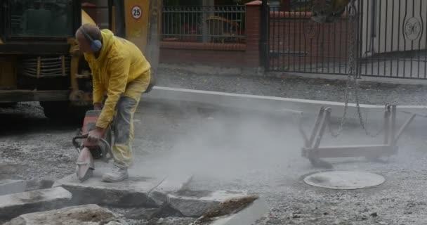 Pracovník člověka v žluté oděvy zblízka je broušení The bloků betonu broušení stroje létající prachu silnice opravy rypadlo na pozadí