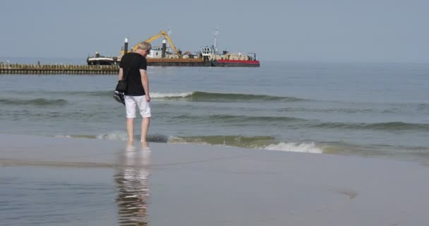 Man With Shoes in Hand Walks Barefoot On The Sea Shore And Wets His Feet In The Water Sea Surf Breakwater In The Distance Construction Barge At The Sea