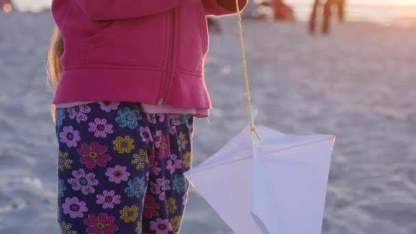 Dívka je hraní s Kite málo večer - lidé pěšky nebo sedí na pláži během festivalu mezinárodní draka v Leba, Polsko