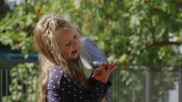 Little Girl With Long Fair Hairs is Playing Ball Swaying Running Girl is Smiling Jumping Park People are Standing Trees Fence on Background Sunny Day
