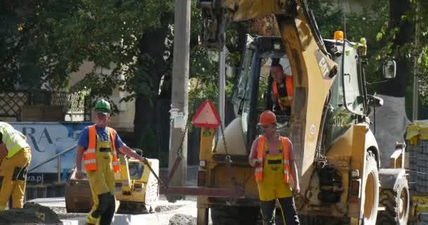 Workers in Yellow Workwear And Safety Helmets are Holding the Loader Hunging on Excavator Scoop Yellow Excavator CAT is Moving Road Repair Sity Street