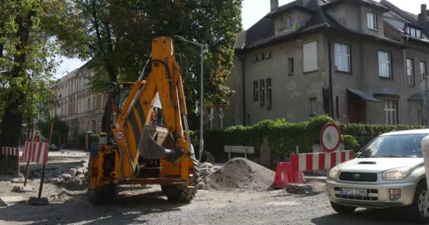 Man is Driving The Yellow Excavator With Flasher Gives the Way Cars Passing By City Street Building Safety Red and White Fence Sunny Day Opole Poland