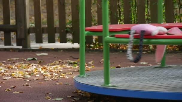 Malá holčička v oranžové tričko a sukni nohy blízko nahoru je rotující kolotoč Toy růžové Tilda králík je na kolotoč hraje na hřišti