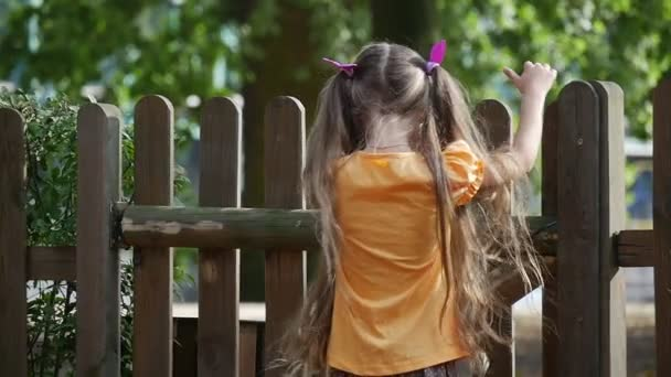 Girl is Climbing to The Wooden Fence Girls Back Slow Motion Little Girl With Long Fair Hairs in Orange T-Shirt is Playing Outdoors at the Playground