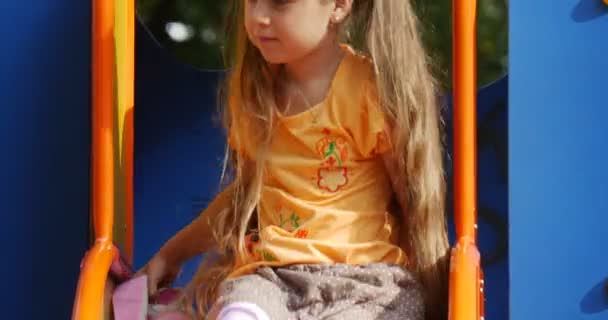 Girl is Sitting on The Chute With Pink Toy Tilda Rabbit Girl is Going Down Little Girl With Long Fair Hairs in Orange T-Shirt is Playing Playground