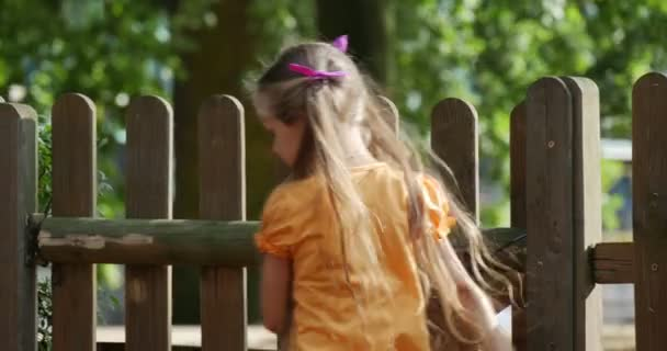 Girl is Climbing to The Wooden Fence Then Goes Out Picks Up the Toy Rabbit Walking Shows the Tongue Little Girl With Long Fair Hairs in Orange T-Shirt