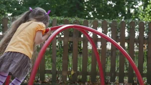Girl is Swinging on The Carousel Slow Motion Little Girl With Long Fair Hairs in Orange T-Shirt is Playing at Playground Wooden Fence Green Trees