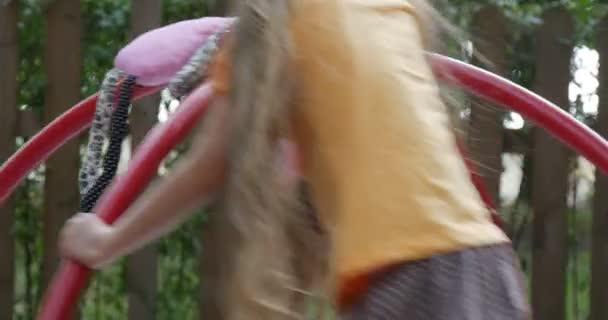 Mädchen schwingt auf dem Karussell mit rosa Spielzeug Tilda Kaninchen kleines Mädchen mit langen blonden Haaren in orangefarbenem T-Shirt spielt auf Spielplatz Holzzaun