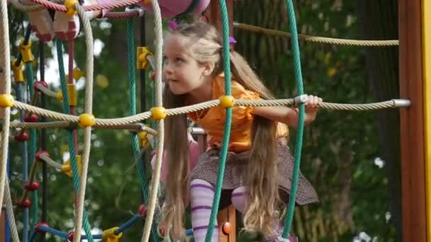 Girl is Walking by the Bridge Through the Rope Stairs Little Girl With Long Fair Hairs in Orange T-Shirt is Playing Outdoors at the Playground Trees