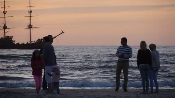Emberek figyelembe fotó pár férfi és a nő a csók család sziluettek a séta mentén a tengerparti strand hajó a tengeri naplemente rózsaszín ég Leba