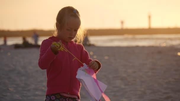 Dívka je zkoumání malého draka večer - lidé pěšky nebo sedí na pláži během festivalu mezinárodní draka v Leba, Polsko