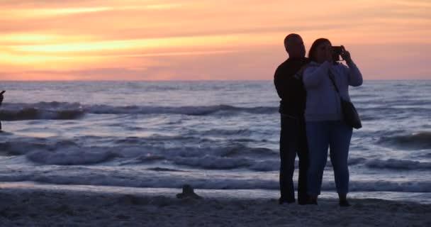Middle Aged Couple prendendo i bambini di famiglie di persone dei Video sono guardando volare aquiloni a piedi da spiaggia uomo che trasporta il Kite Tramonto Kite Festival
