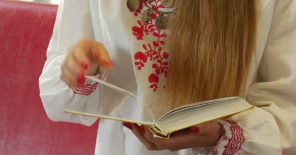 Žena s dlouhými vlasy v vyšívanou bílou košili se nachází na červené pohovce a prohlíží knihu zavřít zobrazení John Paul Ii městské veřejné knihovny v Opole