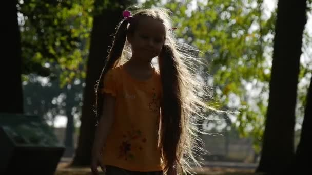 Girl is Turning Around at The Sun Smiling Slow Motion Little Girl With Long Fair Hairs Two Ponytails Lilac Bows Orange T-Shirt Girl at Playground